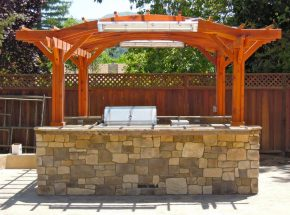 Outdoor kitchen with stone facade and wooden pergola
