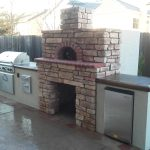 outdoor kitchen with a stone fireplace and pizza oven