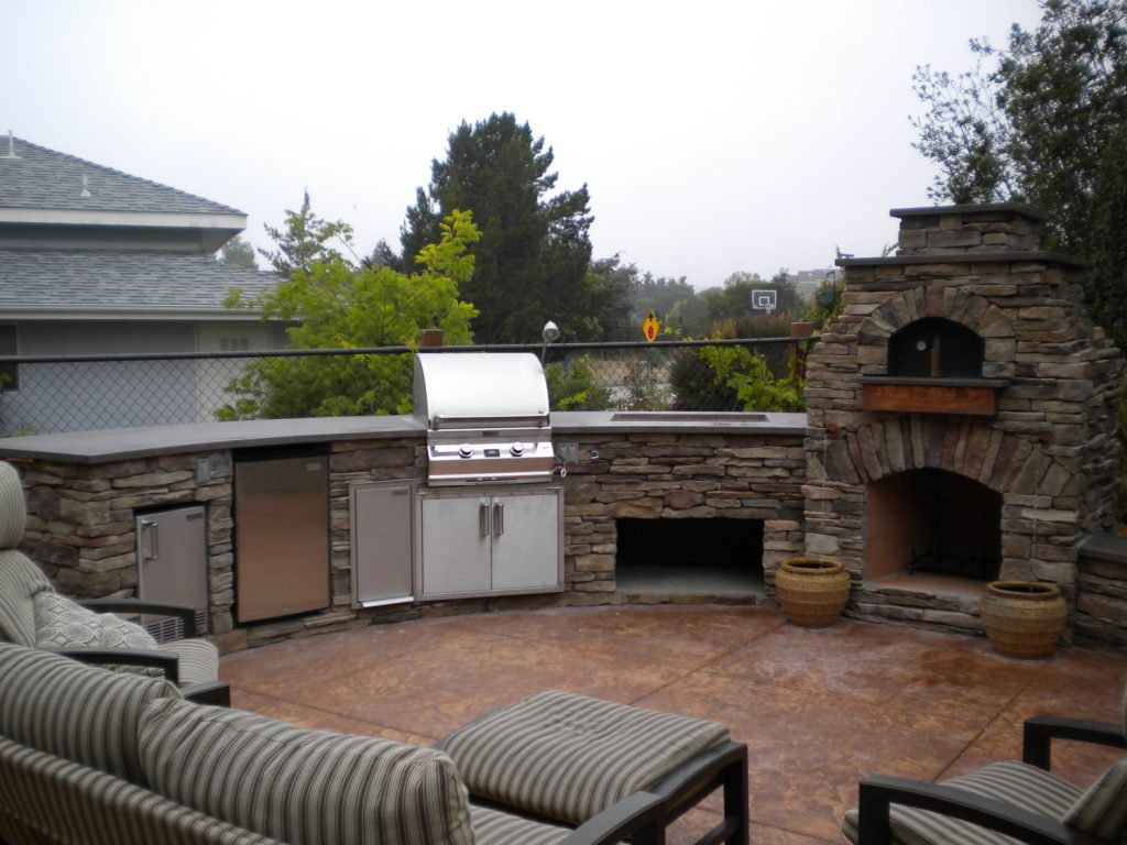 Large outdoor kitchen with a connected stone fireplace and pizza oven