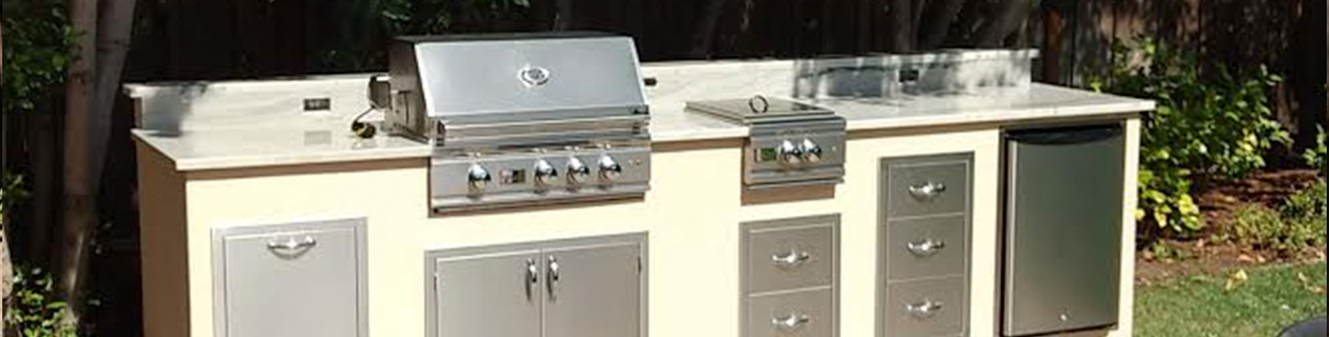 Small outdoor kitchen with gas grill, mini fridge and side burner