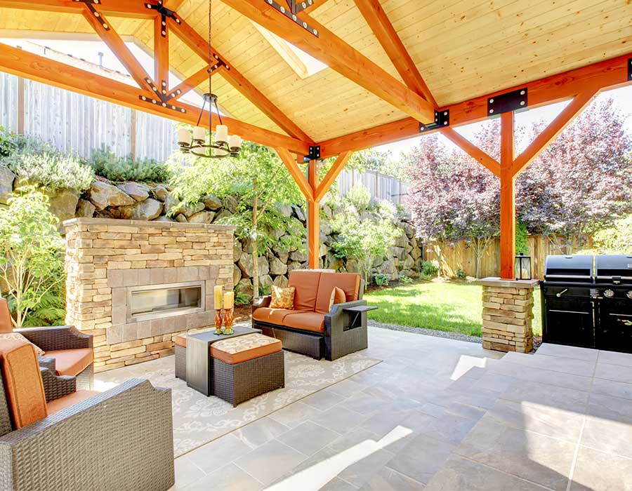 beautiful wood-beamed covered patio with grill and fireplace